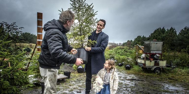 Kweker Frans Kerver (links) overhandigt Joost Keizer en zijn dochter Lena hun boom. Foto: Duncan Wijting