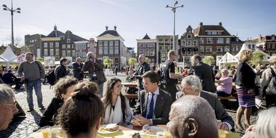 Minister-president Mark Rutte schoof tijdens het Vrijheidsontbijt op de Grote Markt aan bij de tafel van Theo Rellum uit Groningen en zijn dochter Joyce. FOTO ANP/ ROBIN VAN LONKHUIJSEN