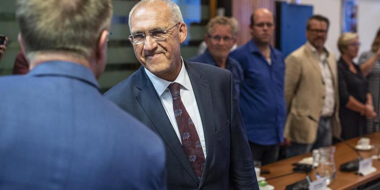 CdK Rene Paas (links, op de rug gezien) feliciteert Adriaan Hoogendoorn als eerste door de kroon benoemde burgemeester van Midden-Groningen. foto Duncan Wijting