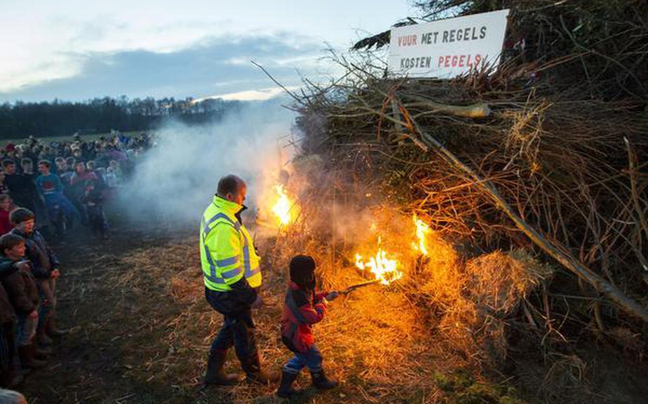 Met een fakkel mag een van de kinderen de bult in brand steken. FOTO HUISMAN MEDIA