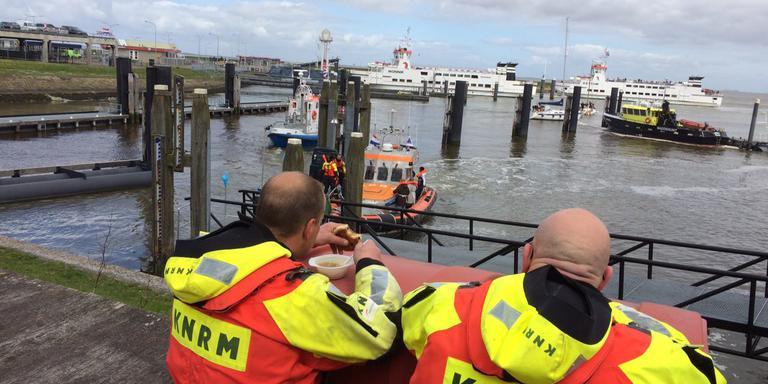 Twee bemanningsleden van het KNMR kijken naar de boot. FOTO DVHN