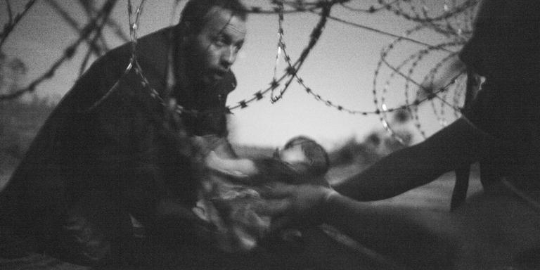 Foto van het jaar: Een man die een baby door het prikkeldraad doorgeeft op de grens van Hongarije en Servië. FOTO WARREN RIDCHARDSON