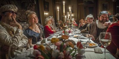 Gasten aan tafel bij het gekostumeerde bal in de Borg Nienoord, ter ere van de vijftigste verjaardag van directeur Geert Pruiksma.