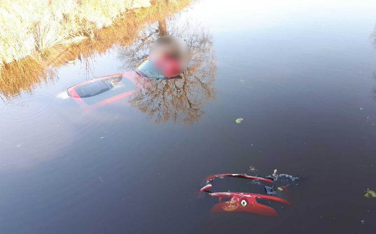 Auto rijdt Oranjekanaal in na botsing op Beilerweg; omstanders halen bestuurder uit het water.