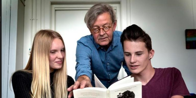 Iris Oord, docent Paul Holthuis en Bjorn Ritsma (vlnr) van het Drachtster Lyceum bekijken het boek waarop de lesmethode gebaseerd is. Foto: Peter Wassing