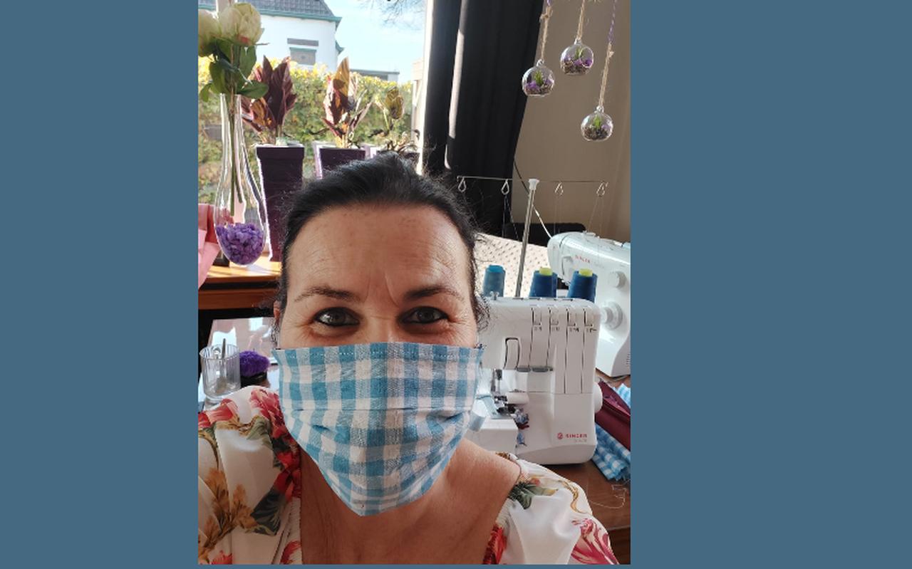 Mirjam van der Laan met een mondkapje en op de achtergrond haar naaimachine.