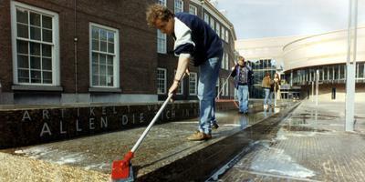 De Grondwetbank tegen het oude gedeelte van het Binnenhof in Den Haag wordt schoongemaakt. Op de bank staat artikel 1 van de Grondwet. Foto: Archief ANP