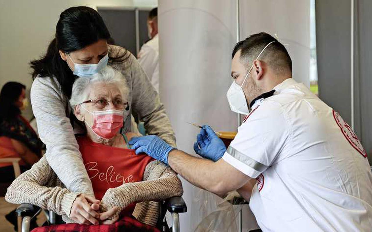 Een oudere vrouw in Israël wordt gevaccineerd.