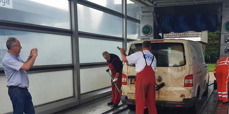 Medewerkers van de wasstraat in Tynaarlo schrobben de teer van de auto's. FOTO H. METER