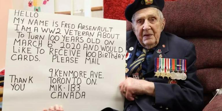 De bijna-honderdjarige Fred Arsenault met zijn tekstbord.