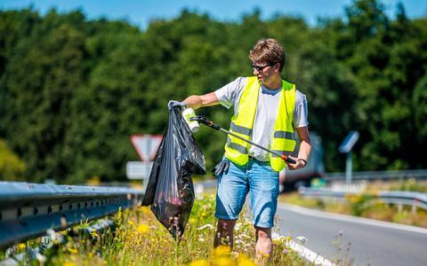 Verslaggever Bas van Sluis prikt in drie uur tijd vijftien kilo zwerfafval uit de berm langs de N33 tussen Assen en Gieten