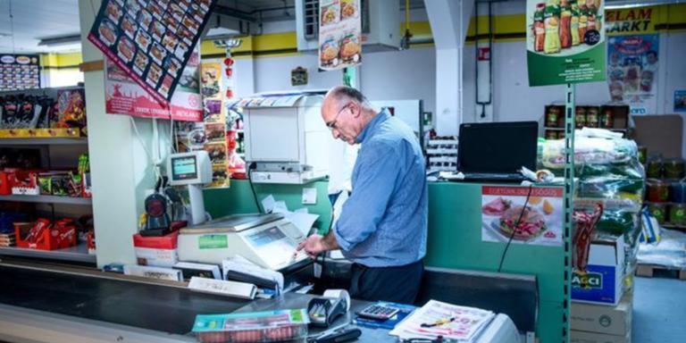 Winkeleigenaar Mustafa Onlu achter de kassa.