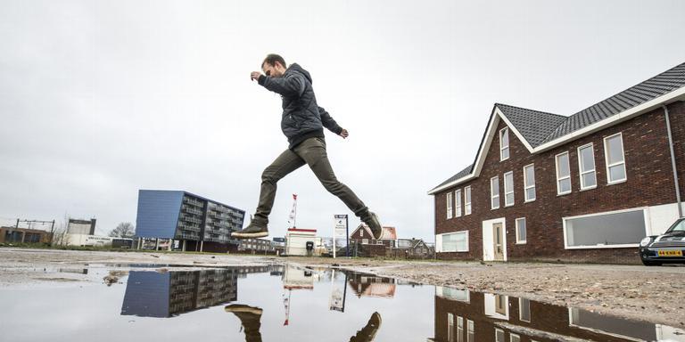 Bewoner Chris Dirksen moet over de plassen heenspringen om op straat te komen