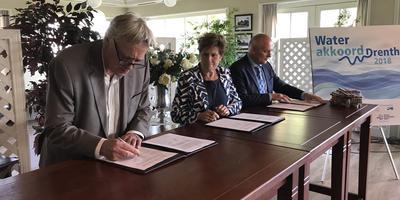 Hans Pereboom van WDOD, Ria Broeze van Vechtstromen en gedeputeerde Henk Brink ondertekenen de overdracht van het peilbeheer. Foto: DvhN