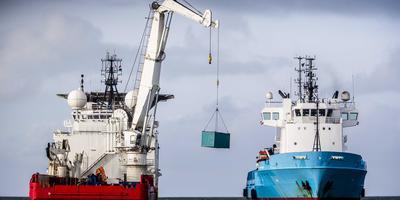 Een schip van de Kustwacht bergt een overboord geslagen container van MSC Zoe.