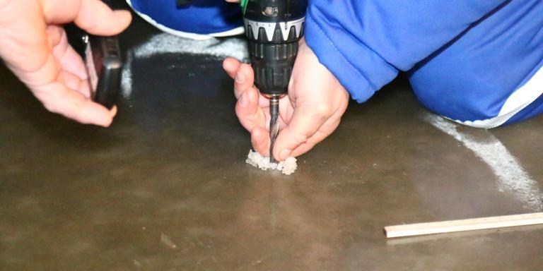 De ijsmeester boort in het ijs om de dikte te testen. FOTO HERMAN VAN OOST