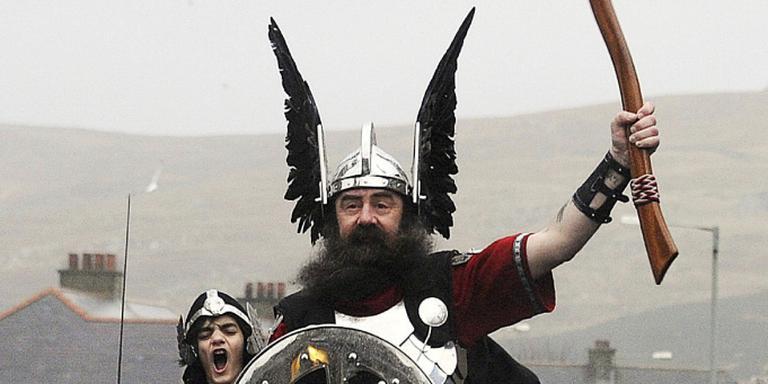 'Viking' in Lerwick heft zijn bijl. FOTO AFP/ANDY BUCHANAN