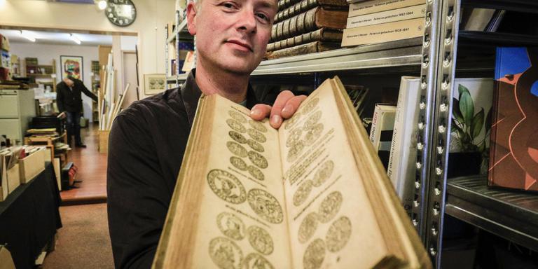 Michel de Vries toont een bijzondere muntencatalogus uit 1630. FOTO JAN WILLEM VAN VLIET