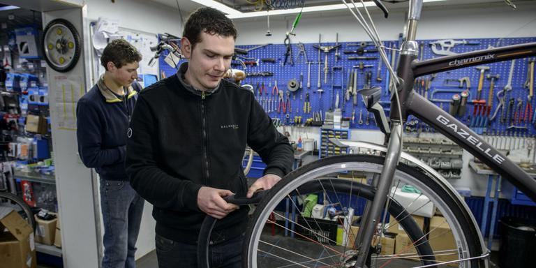 Bij fietsenhandelaar Stuurwold worden lekke banden nog geplakt en niet zoals steeds vaker het geval is gewoon vervangen. Jan Verheul en Danny Pluim plakken banden en repareren fietsen. Foto: Jan Zeeman
