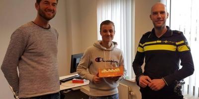 Daan met gebak tussen de bedrijfsleider van de telefoonwinkel en de agent. Foto: Politie Meppel