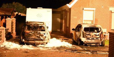 De twee uitgebrande auto's in Emmen. Op de achtergrond de caravan die gespaard bleef.