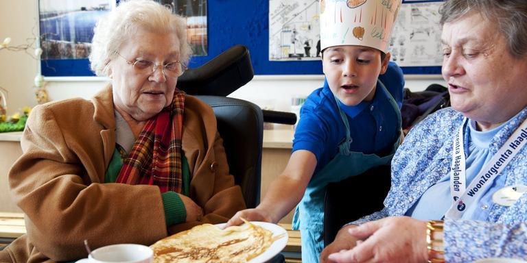 Een Haagse scholier serveert een pannenkoek in een verzorgingstehuis tijdens Nationale Pannenkoekdag.