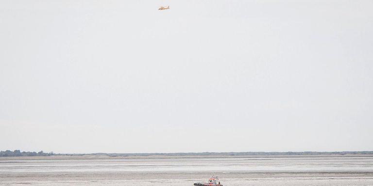 Een boot van de KNRM en een helikopter zoeken op het wad naar drie kano's. Foto: De Vries Media