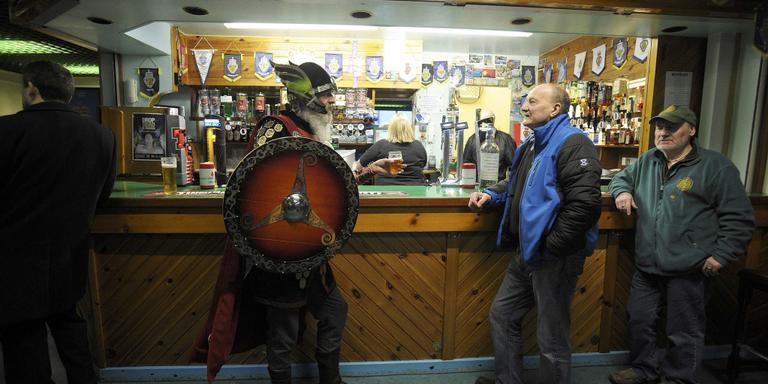 Een deelnemer uitgedost als viking drinkt een biertje voor de start van het Up Helly Aa Festival. FOTO ANDY BUCHANAN