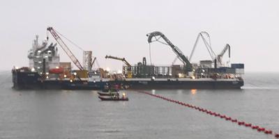 De kabel wordt aan land gebracht. Foto: DvhN