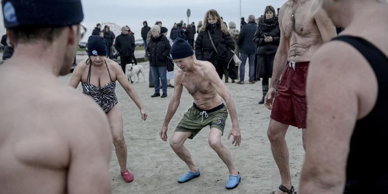 De deelnemers doen voorafgaand aan de nieuwjaarsduik nog een aantal oefeningen om warm te blijven. Foto Jan Zeeman