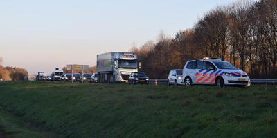 De politie is inmiddels ter plaatse. Op de achtergrond is de forse file te zien. Foto: De Vries Media