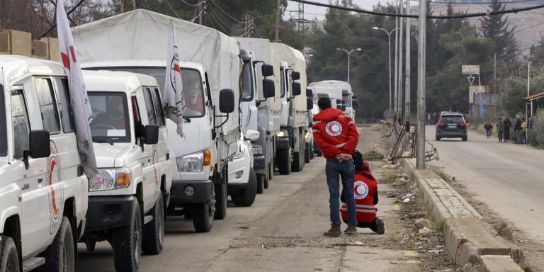 Een hulpkonvooi van het Rode Kruis wacht tot het noodhulp kan verlenen in de Syrische stad Madaya. Foto: AFP
