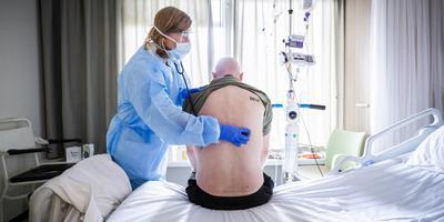 Een internist luistert naar de longen van een coronapatient die herstellende is van IC-opname.