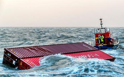 Een sleepboot brengt twee overboord geslagen containers van het schip MSC Zoe de haven binnen. Het containerschip MSC Zoe verloor in de nieuwjaarsnacht 281 containers in de Noordzee.