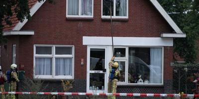 De brandweer slaat de ruiten van de woning in.