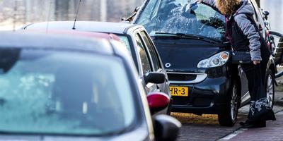 Een vrouw krabt de ruit van een auto schoon.