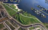 Landschapskunst in Meerstad: dwars door het nieuwe landartpark aan de oevers van het Woldmeer kronkelt een witbetonnen fietspad ,,als een kettingsnoer door het landschap''.