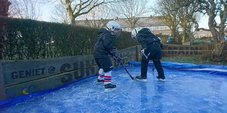 De kleinkinderen van André Hup aan het ijshockeyen op de zelfgemaakte baan. Foto: Eigen foto