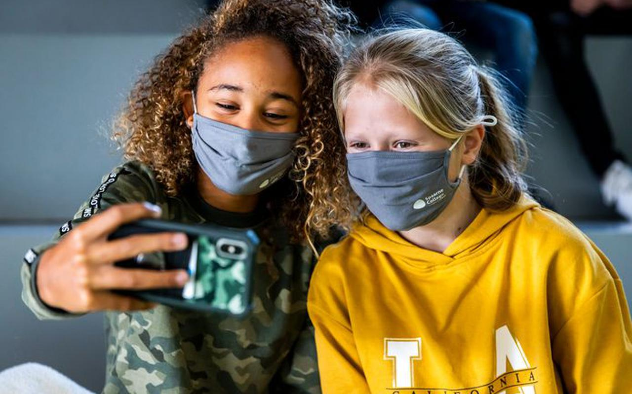 Leerlingen van een middelbare school maken een selfie met hun mondkapje tijdens de pauze.