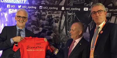 De gedeputeerden van Drenthe, Henk Brink en Henk Jumelet, bieden Brian Cookson het Drenthe Beweegt-wielershirt aan.