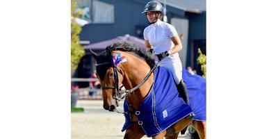 Chantal Regter maakt met haar paard Enjoy een ereronde.