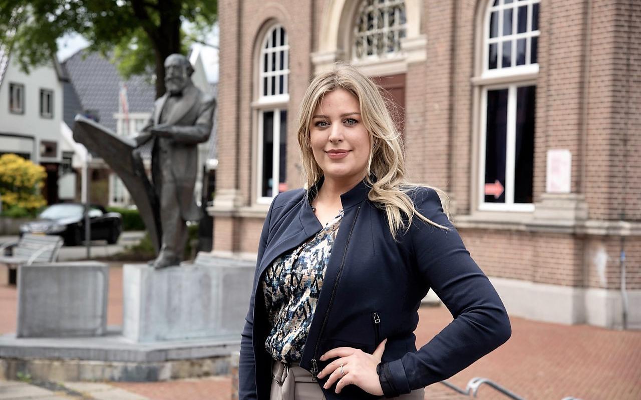 Celine Vister voor het Veenkoloniaal Museum met op de achtergrond het standbeeld van Anthony Winkler Prins.