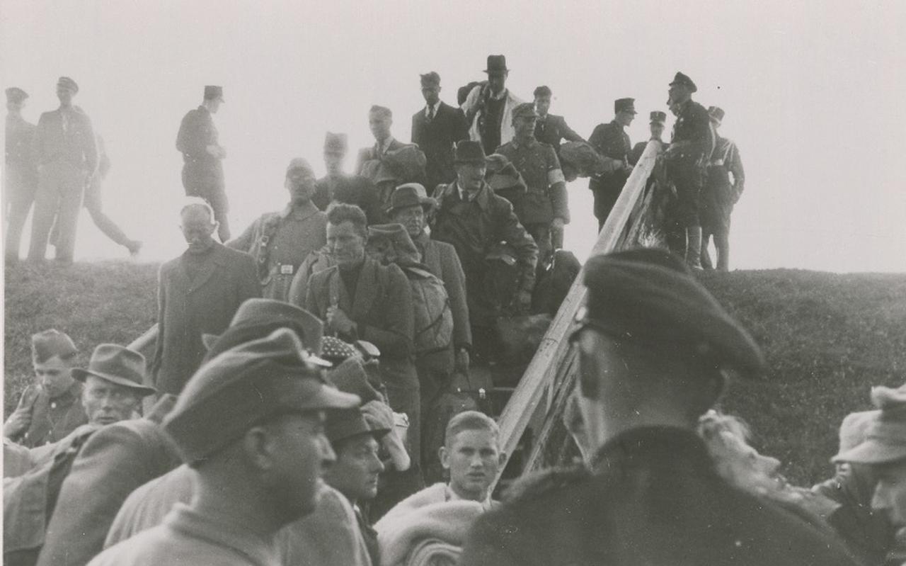 Duitse soldaten en hun Nederlandse bondgenoten komen aan in Zoutkamp, nadat ze zijn gearresteerd door de Canadezen.
