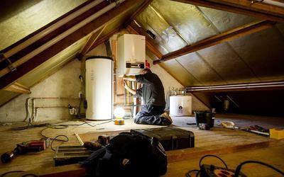 De installatie van een warmtepomp bij een verwarmingsketel.