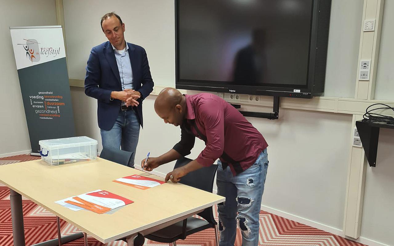 Idris Salih Ibrahim uit Eritrea ondertekent zijn certificaat van de arbeidsmarkttraining van Vluchtelingenwerk Noord-Nederland. Hij werkt nu als dakdekker. Links wethouder Jeroen Westendorp.