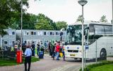 Bewoners van het azc in Delfzijl stappen in de bus richting Musselkanaal.