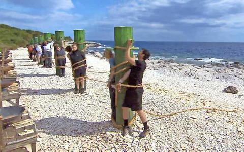 De deelnemers moeten zichzelf zien los te maken van grote palen.