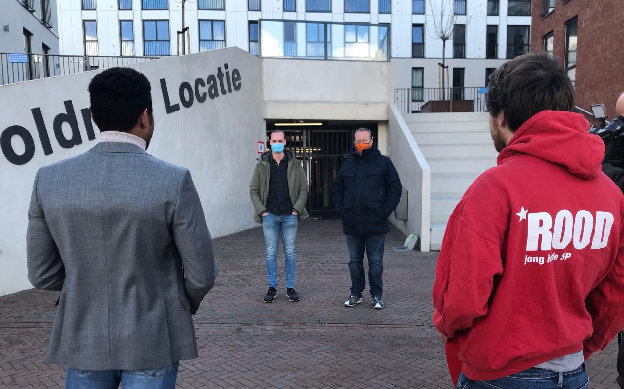 Huurder Dennis Lo (links) en ROOD-lid Hans de Waard bieden Woldring-directeur André van Dalsen (met oranje mondkapje) het zwartboek met huurdersklachten aan.