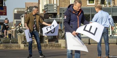 Ondernemers zijn op de Markt in de weer met het leggen van de letters. Op de voorgrond voorzitter Richard Dimmendaal van de Coevorder Handelsvereniging.