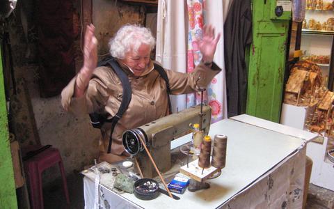 Een uitgelaten Gré Vos, toen zij in Jeruzalem deze naaimachine tegenkwam en er even achter mocht.